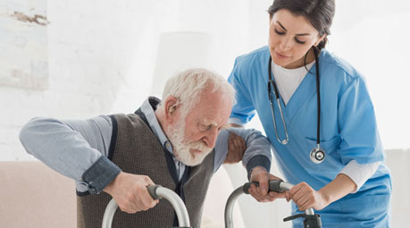 Nurse helping an elderly man with a walker to get up at his home | Specialized Services | Miami FL 33165 | call 305-220-1088