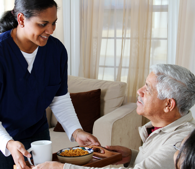 Nurse serving lunch to an elderly man at home | Medicaid Services | Miami FL 33165 | call 305-220-1088