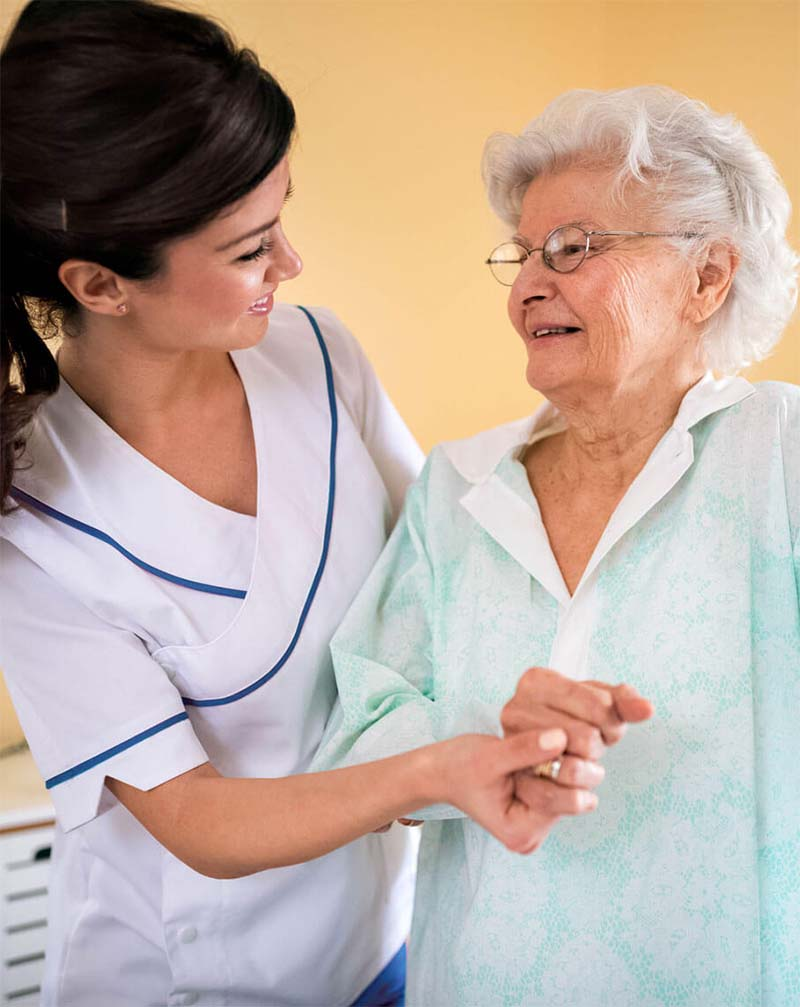 Nurse helping elderly lady to stand up and walk at her house